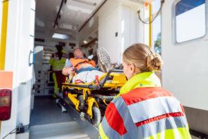 Paramedics in uniform putting injured man on stretcher in ambulance car